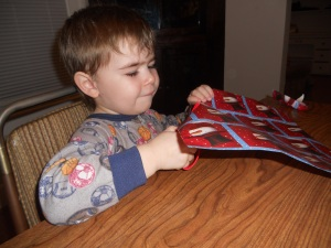 Using his new scissors to cut some wrapping paper.