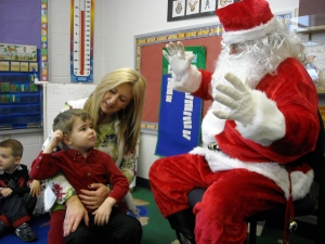 Mrs. P holds a cautious yet curious Philip beside Santa Claus