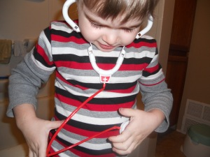Philip uses his toy stethoscope, just like the doctor did that morning